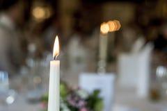 燃烧的白色蜡烛浪漫饭桌记忆特写镜头纪念在bokeeh背景前面 免版税库存照片