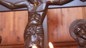 燃烧的蜡烛在耶稣受难象和象的背景的修道院里 股票视频