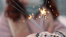 燃烧的闪烁发光物在妇女的手,选择聚焦上 股票录像