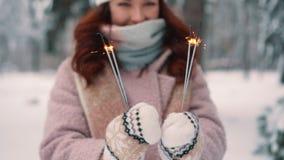 燃烧的闪烁发光物在妇女的手,选择聚焦上 影视素材