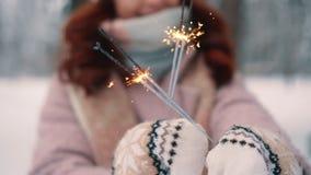 燃烧的闪烁发光物在妇女的手,选择聚焦上 股票视频