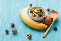 燕麦剥落用樱桃、猕猴桃、黑莓、鸡蛋、核桃和蜂蜜在小杯子在绿松石木桌上 免版税库存图片