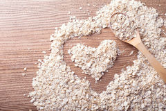 燕麦和心脏在木背景中 免版税库存图片