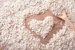燕麦和心脏在woodwn背景中与木匙子 免版税库存图片