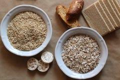 燕麦和米在碗 米糕和面包在背景中 高碳水化合物的食物 免版税库存图片