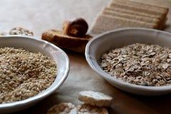 燕麦和米在碗 米糕和面包在背景中 高碳水化合物的食物 免版税库存照片