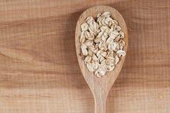 燕麦在一个木板的一把匙子剥落 免版税库存照片