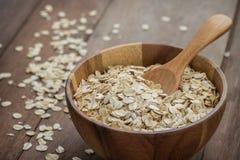 燕麦在木碗剥落 库存图片