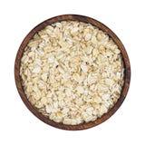 燕麦在白色背景隔绝的木碗剥落 顶视图 免版税库存照片