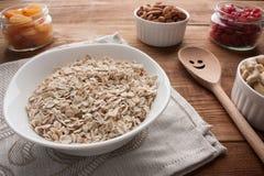 燕麦在碗剥落用杏干,干樱桃,杏仁,在瓶子的腰果在与木匙子的木桌上 免版税库存图片