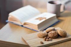 燕麦曲奇饼、杏仁和书在桌上在家 库存图片