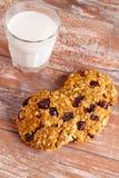 燕麦曲奇饼用蔓越桔和杯牛奶 免版税库存图片