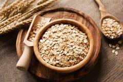 燕麦片,有机燕麦在木碗和金黄麦子耳朵剥落在木背景 免版税库存图片