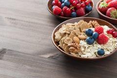 燕麦粥、格兰诺拉麦片、坚果和莓果在木背景 免版税库存照片