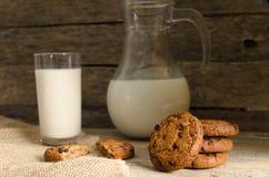 燕麦粥巧克力曲奇饼、水罐和杯牛奶,土气木背景 库存照片