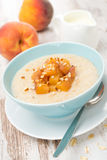 燕麦粥用在碗和水罐的焦糖的桃子酸奶 免版税库存照片