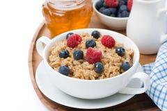燕麦粥用新鲜的莓果和蜂蜜,特写镜头,被隔绝 库存照片