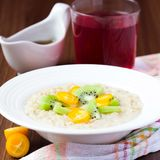燕麦粥用果子,桔子, cumquat,猕猴桃,枫蜜 免版税库存照片