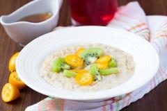燕麦粥用果子,桔子, cumquat,猕猴桃,枫蜜 免版税图库摄影