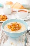 燕麦粥用焦糖的桃子、茶和酸奶早餐 免版税库存照片