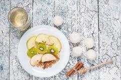 燕麦粥用苹果、梨、核桃和猕猴桃在一个白色碗 顶视图 库存图片