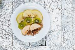 燕麦粥用苹果、梨、核桃和猕猴桃在一个白色碗 顶视图 免版税库存照片