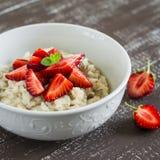 燕麦粥用蜂蜜和草莓在一个白色碗在一张黑暗的木桌上 图库摄影