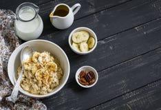 燕麦粥用香蕉、焦糖调味汁和山核桃果在一个白色碗黑暗的木表面上 图库摄影