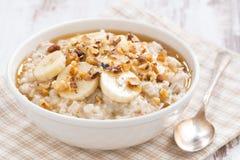 燕麦粥用香蕉、蜂蜜和核桃在碗 免版税图库摄影