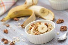 燕麦粥用香蕉、蜂蜜和核桃早餐 免版税库存照片