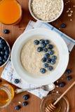 燕麦粥粥、莓果、蜂蜜和新鲜的汁液健康早餐  免版税库存图片