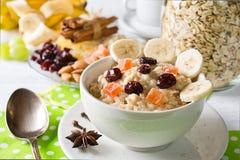 燕麦粥粥用干果子、蔓越桔、香蕉和香料 瓶子在背景的燕麦粥 库存图片