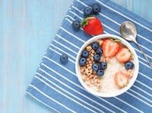 燕麦粥粥用新鲜的草莓,蓝莓,在对比蓝色背景的格兰诺拉麦片 Healty早餐顶视图 免版税库存图片