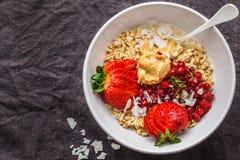燕麦粥粥用莓果、花生酱和椰子在白色碗,黑暗的背景 健康素食主义者食物概念 免版税图库摄影
