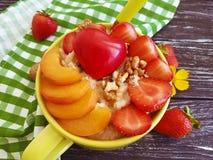 燕麦粥粥,杏子,草莓,在木背景的心脏 免版税库存照片