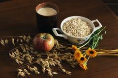 燕麦耳朵词根和燕麦剥落在一个白色罐、万寿菊花和杯子牛奶和苹果在黑褐色木头桌上 顶视图 燕麦f 免版税库存照片