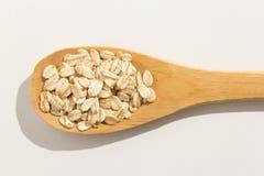 燕麦谷粒 在一把木匙子的滋补五谷在白色b 图库摄影