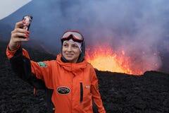 爆发在堪察加,女孩的扎尔巴奇克火山火山拍摄了在背景熔岩湖的selfie火山口火山的 免版税库存图片