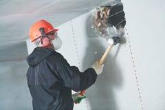 爆破工作和重新整理 有大锤毁坏的墙壁的工作者 库存照片