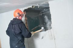 爆破工作和重新整理 有大锤毁坏的墙壁的工作者 图库摄影