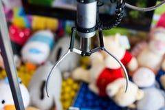 爪起重机捕获设备在孩子的游乐园 玩具俘获器比赛在孩子公园 爪起重机与迷离的比赛概念 库存照片