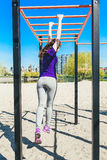 爬一架水平的梯子的蓝色T恤杉的年轻美丽的深色的女孩在公园 免版税库存图片