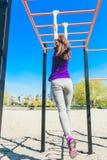 爬一架水平的梯子的蓝色T恤杉的年轻美丽的深色的女孩在公园 库存照片