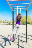 爬一架水平的梯子的蓝色T恤杉的年轻美丽的深色的女孩在公园 库存图片