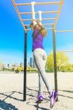爬一架水平的梯子的蓝色T恤杉的年轻美丽的深色的女孩在公园 免版税库存照片