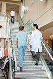 爬上台阶的医生和护士在医院 免版税图库摄影