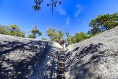 爬上在一串足迹的一张陡峭的岩石面孔使用梯子 免版税库存照片