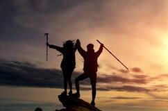 爬上山峭壁和他们中的一个的男性和女性远足者给帮手 库存图片