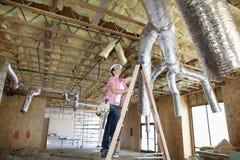 爬上梯子的少妇,当看天花板时 免版税库存图片