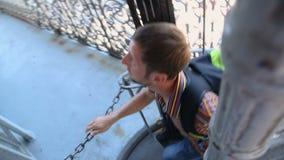爬上紧的螺旋形楼梯的背包徒步旅行者看从俯视图的城市 影视素材